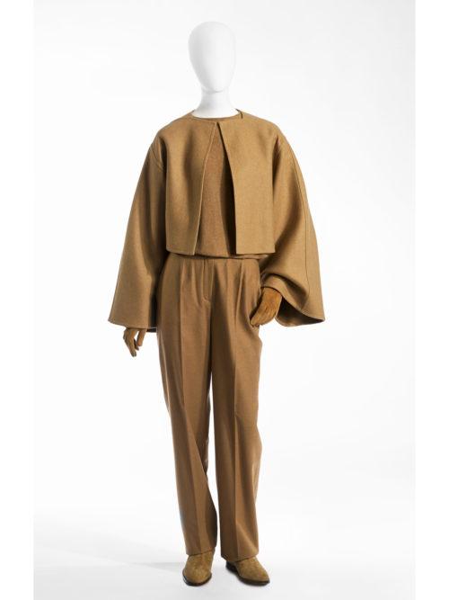 Dubbelzijdige kasjmieren mantel met wijde mouwen gedragen op een naadloze kasjmieren trui met vleermuismouwen op een broek van kameelhaar.