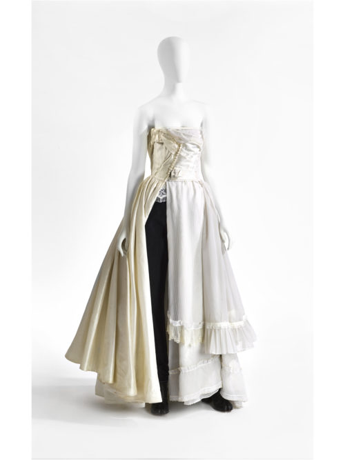 Evening gown made out of three vintage wedding dresses worn on a groom's trousers. Martin Margiela presented this silhouette in his Autumn-Winter 2005-2006 collection.
