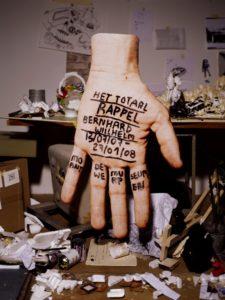 Affichebeeld voor de tentoonstelling BERNHARD WILLHELM: HET TOTAAL RAPPEL. Een hand met titelopschrift zweeft boven een tafel met verfpotten, resten piepschuim en andere materialen.