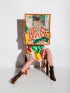 Een vrouwenfiguur in een fel gekleurde jurk door Dirk Van Saene zit op een stoel met een schilderij op haar schoot. Het schilderij is Lezende Vrouw van Rik Wouters, gemaakt in 1913