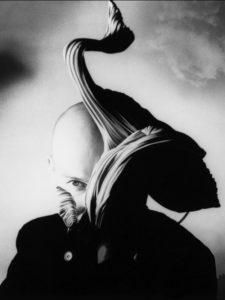 Affichebeeld voor de tentoonstelling STEPHEN JONES & Het Accent op Mode. Een zwart/wit portretfoto van Stephen Jones die een van zijn sculpturale creaties draagt.