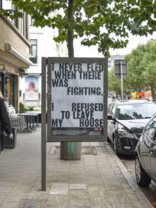 Billboard met quote 'I never fled when there was fighting. I refused to leave my house'.