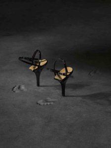Affichebeeld voor de tentoonstelling FOOTPRINT. Een paar Heel-only schoenen laat voetsporen na in het donkergrijze zand.
