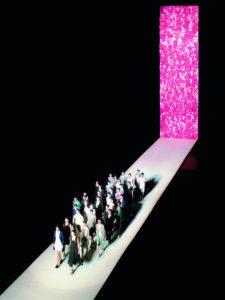 Een dertigtal modellen loopt de finale op de catwalk van Dries Van Noten met een roze achtergrond vol bloemen.
