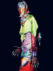 Affichebeeld voor de tentoonstelling Happy Birthday Dear Academie. Een model is van kop tot teen gewikkeld in kleurrijke sjaals buiten haar handen. Deze zijn bedekt met kant en hebben klauwachtige nagels.