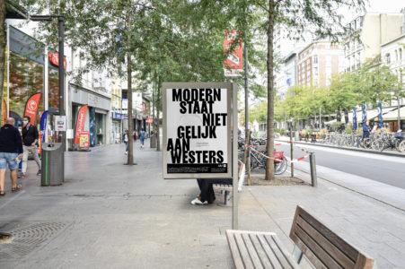 Billboard met quote 'Modern staat niet gelijk aan westers'. Billboard staat in de Keyserlei, Antwerpen