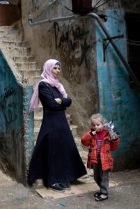Vrouw staat voor haar huis in Libanon met haar dochter