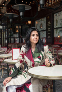 Zolaykha Sherzad sitting at a table outside a cafe