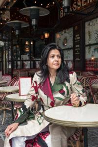 Zolaykha Sherzad zit aan een tafel buiten een cafe