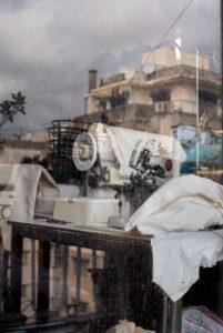 Achter het raam zie je een naaimachine