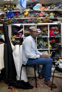 Kleermaker Idriss zit op een stoel in zijn atelier