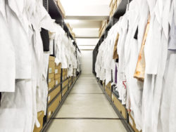 Image of the collection depot in MoMu with wardrobes on both sides in which museum objects hang or lie down in bags or boxes.