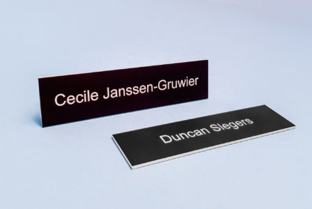 Two black plaques with white letters on a grey background.