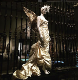 Silhouette in the Heavenly Bodies exhibition at the Met Museum including gold feathery Thierry Mugler angel wings restored by MoMu's collection department