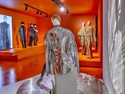 Image of the exhibition in MoMu. In the foreground a mannequin in a silver silhouette by Maison Martin Margiela.