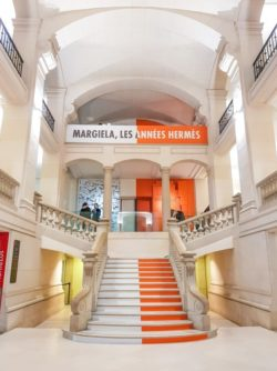 Entrance hall of MAD Paris with a staircase. The left part of the staircase is white and represent Martin Margiela. The right part is orange and represents Hermès