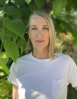 Model Kristina De Coninck in een wit t-shirt omringd door groene bladeren