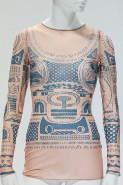 Doorschijnend nude shirt met lange mouwen. Bedrukt met een blauw patroon