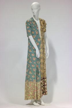 Lange jurk met korte mouwen op mannequinpop. Jurk met bloemenmotieven