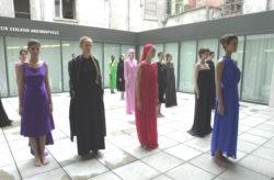 Binnenkoer van MoMu met 13 modellen gekleed in kleurrijke en sobere jurken van Patrick Van Ommeslaeghe