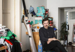 Klaas Rommelaere in his studio sitting on chair surrounded by his (un)finished work