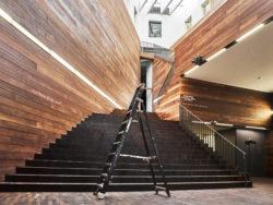 De afbeelding toont het vooraanzicht van de beruchte MoMu-trap. Een ladder staat in het middel van de hal.