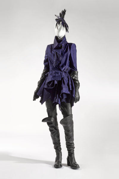 Mannequin dressed in dark purple coat, leather gloves and headpiece with feathers