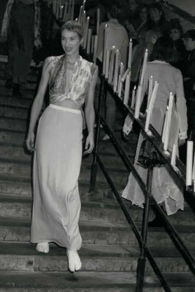 fashion show at Paris's abandoned Saint-Martin Metro Station, model walking down the stairs passing by a railing with lit candle lights