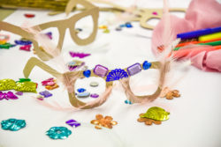 Paper glasses made by children in the Olivier Theyskens exhibition, ornamented with pink feathers and purple and blue glitter and stones.