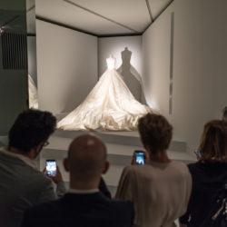 groep mensen staan voor een bruidsjurk in de expo