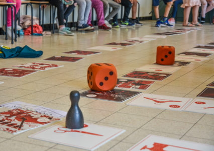 detail of the game, different tiles on the ground with dice and pawn
